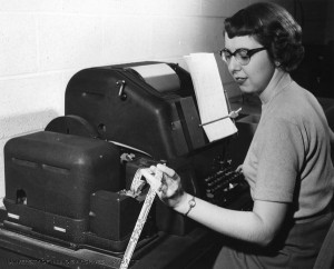 Computer typewriter operator Caroline Brown punches data and instructions on paper tape which is could be processed by ILLIAC at two feet/second (1954). Found in Record Series 39/2/20, Box 177.