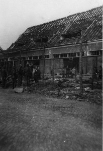 Prisoners and soldiers stand near rows of the dead in Dora-Mittelbau compound.